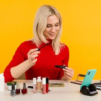 Colpo schietto di blogger carina giovane donna caucasica che presenta prodotti di bellezza e trasmette video in diretta ai social network, usando il pennello per applicare il mascara durante la registrazione del tutorial di trucco quotidiano