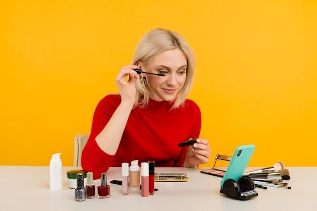 Colpo schietto di blogger carino giovane donna caucasica che presenta prodotti di bellezza e trasmette video in diretta