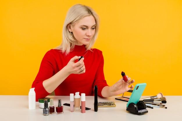 Colpo schietto di blogger carino giovane donna caucasica che presenta prodotti di bellezza e trasmette in diretta