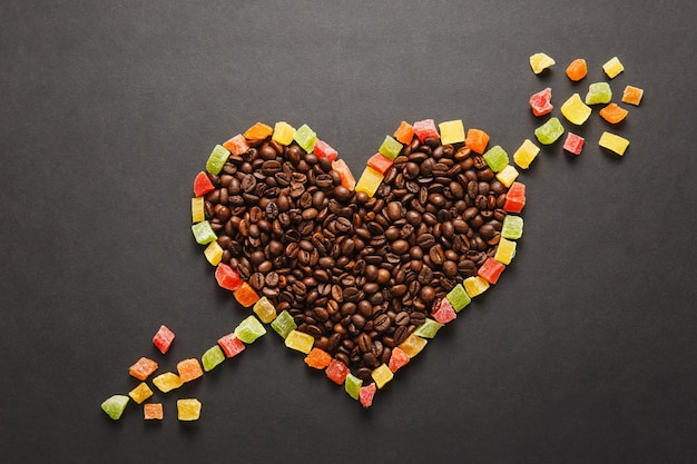 Frutta candita a forma di cuore con freccia, chicchi di caffè marroni isolati su sfondo nero per il design. carta di san valentino il 14 febbraio, concetto di vacanza. copia spazio per la pubblicità.
