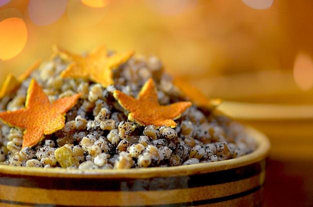 Arancia candita a forma di stella su dessert kutia. la stella è uno dei simboli del natale.