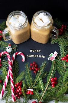 Caramelle e cacao con marshmallow su sfondo nero con i rami degli alberi. l'iscrizione buon natale.