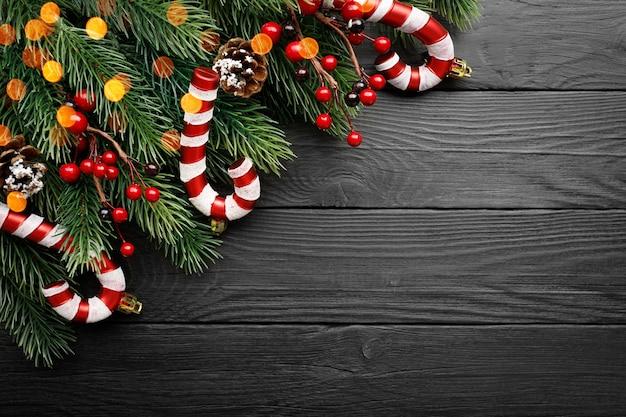 Caramelle, ramo di abete, coni e bacche rosse sulla superficie del legno nero