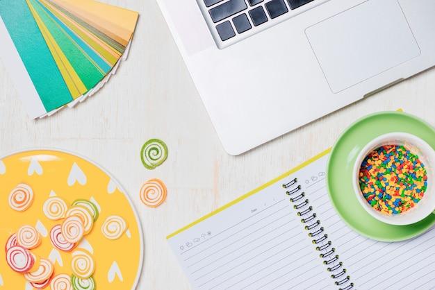 Caramelle, cuffie e blocco note sul tavolo di legno. spazio aperto per la copia.