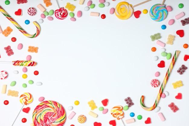 Caramelle e dolci su uno sfondo colorato vista dall'alto con posto per il testo