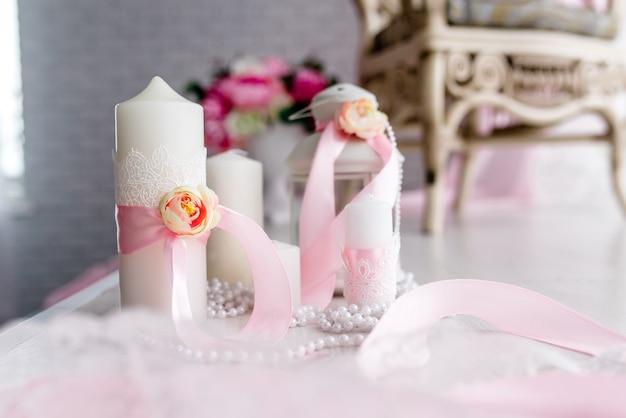 Le candele sono decorate con fiocco rosa, nastro e verdi stanno sul tavolo festivo degli sposi coperti da una tovaglia. laici piatta. vista dall'alto. ispirazione per matrimoni. avvicinamento. opera d'arte. decor. dettagli.