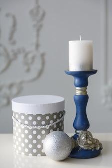 Candela in candeliere blu su sfondo bianco