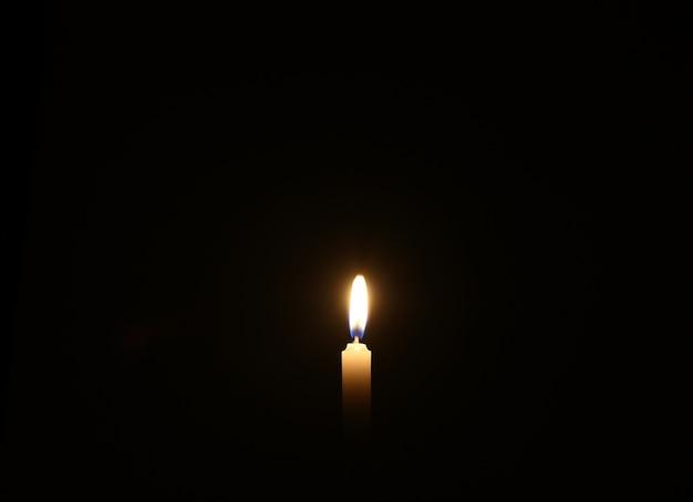 La candela sta bruciando contro il muro nero