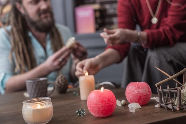 Lume di candela. messa a fuoco selettiva di una bellissima candela in piedi sul tavolo con un indovino professionista e il suo visitatore sullo sfondo