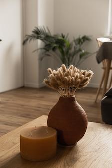 Candela, bouquet di erba di coda di coniglio in vaso di argilla sul tavolo