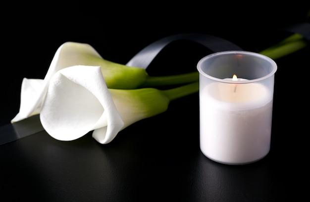 Candela accanto a un fiore bianco su fondo nero