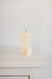 Candela a forma di torso di donna in atmosfera moderna interna bianca e copyspace