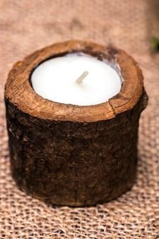 Candela in un candeliere di legno su uno sfondo romantico.