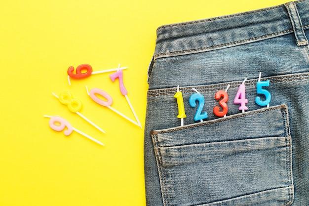 Candele che spuntano dalla tasca posteriore dei jeans blu su sfondo giallo