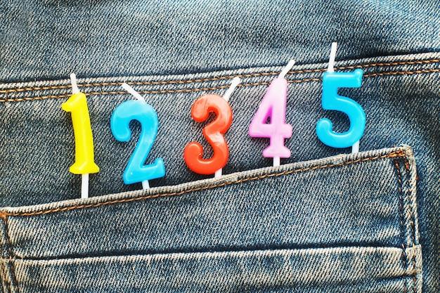 Candele che spuntano dalla tasca posteriore dei jeans blu