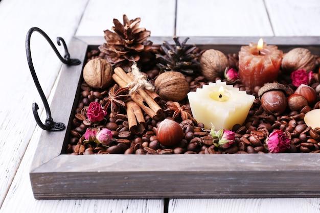 Candele su vassoio vintage con chicchi di caffè e spezie, protuberanze su fondo in legno colorato