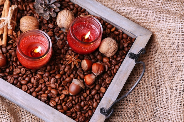 Candele su vassoio vintage con chicchi di caffè e spezie, protuberanze su sfondo di sacco