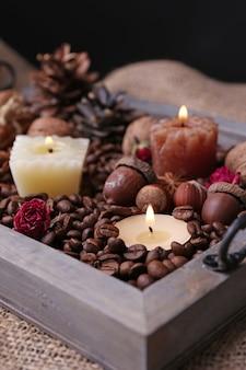 Candele su vassoio vintage con chicchi di caffè e rilievi di spezie su sfondo di sacco