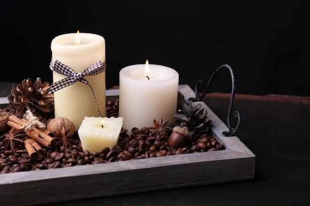 Candele su vassoio vintage con chicchi di caffè e spezie, protuberanze su tavolo di legno, su sfondo scuro