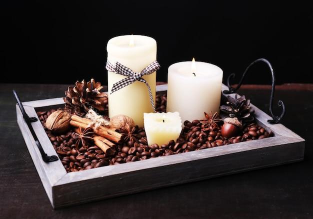 Candele su vassoio vintage con chicchi di caffè e rigonfiamenti di spezie su tavola di legno su sfondo scuro