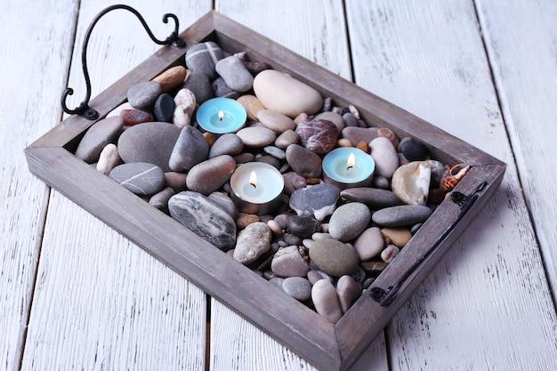 Candele su vassoio vintage con ciottoli di mare, su fondo in legno