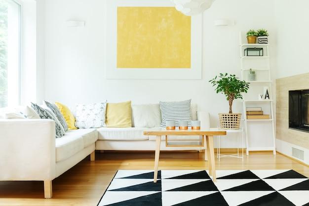 Candele su tavolo in legno e divano beige con cuscini fantasia in interni caldi con pianta su sgabello e pittura gialla sul muro