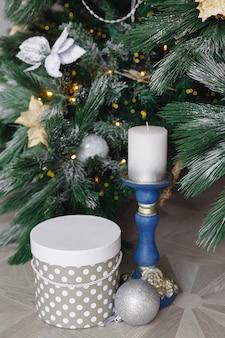Candeliere con candela e confezione regalo sotto l'albero di natale