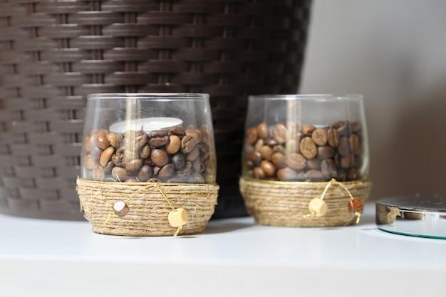 Candelieri con chicchi di caffè, decorati con portacandele in vetro corda marrone.