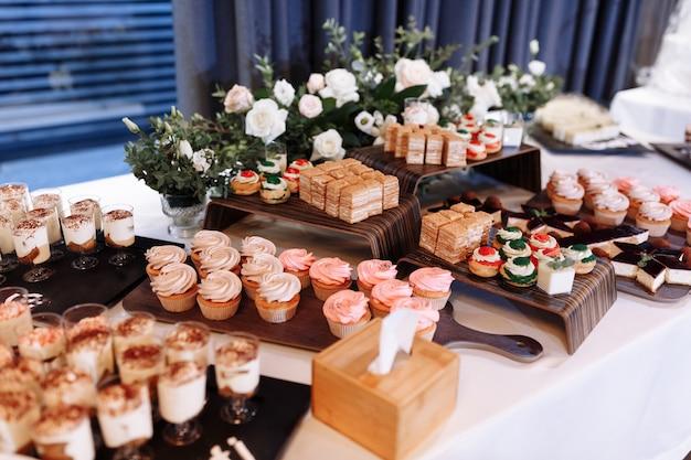 Candy bar decorato da delizioso buffet di dolci con cupcakes, bignè, dolcezza e fiori e altri dolci, caramelle, tavolo da dessert per un matrimonio o una festa di compleanno.