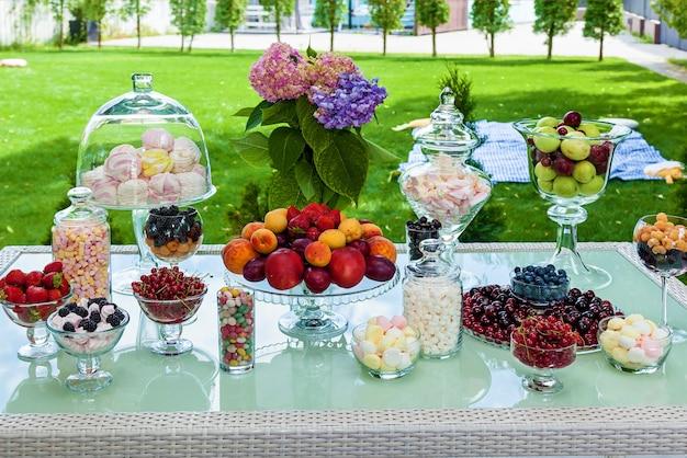 Candy bar di frutta, bacche e marshmallow per una festa. tavola festiva con snack dolci e fruttati