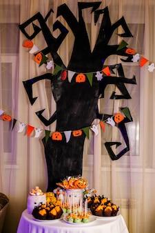 Candy bar con dolci per la celebrazione di halloween. enorme albero nero con decorazioni sullo sfondo