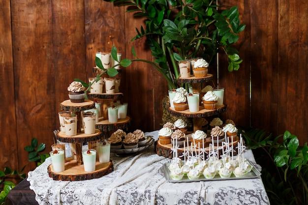 Candy bar sulla festa di nozze in legno con un sacco di soufflé e torte cupcakes caramelle diverse