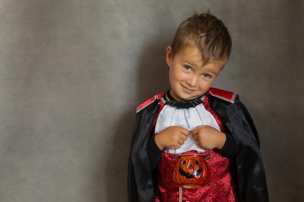 Ragazzo di caramelle in costume da vampiro di halloween su grigio