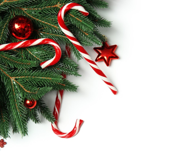 Bastoncini di zucchero e decorazioni natalizie su sfondo bianco