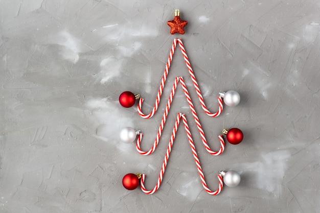 Bastoncini di zucchero a forma di albero di natale con stella e palla su grigio.