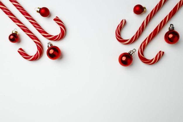 Bastoncini di zucchero e palline di natale rosse su bianco piatto laico, vista dall'alto