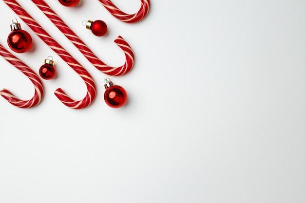 Bastoncini di zucchero e bagattelle rosse di natale su bianco