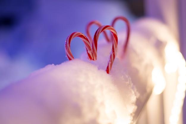 Bastoncini di zucchero a forma di cuore sullo sfondo festivo di natale della neve