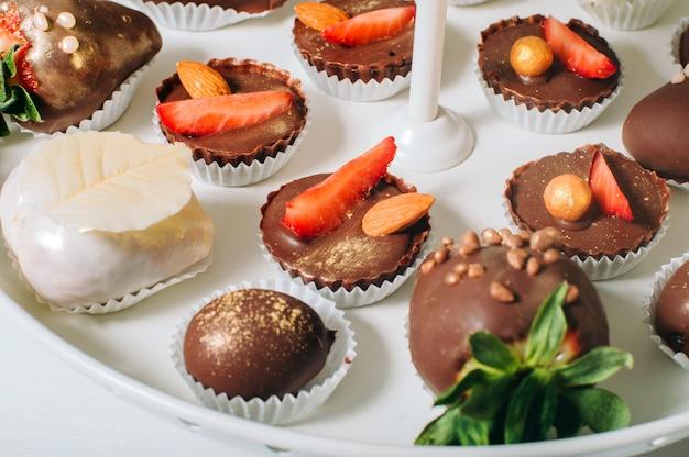 Caramella decorata con fragole, oro commestibile, riso soffiato e mandorle