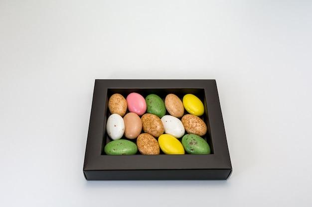 Confetti di caramelle in una glassa multicolore in una scatola su bianco