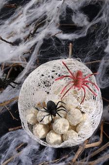 Palline di waffle di caramelle a forma di uova di ragno in un bozzolo con un ragno sul tavolo per halloween