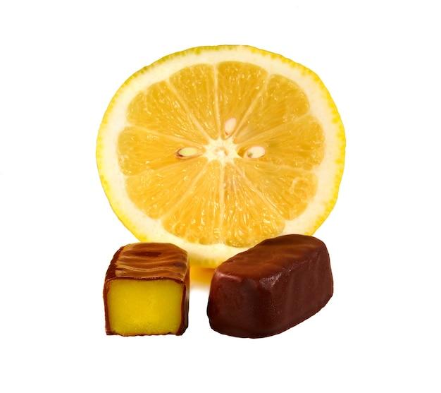 Caramella con ripieno di crema al limone e fetta di limone fresco su superficie bianca