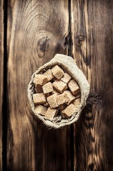 Zucchero di canna raffinato in busta. sullo sfondo di legno.