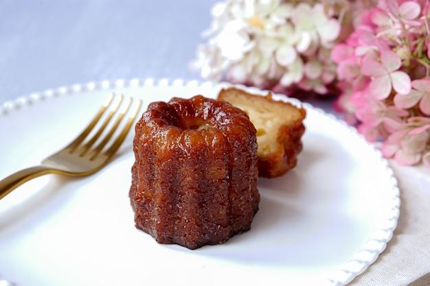 Canele, pasticceria francese, su un piatto bianco, con un pezzo tagliato, forchetta e fiori di ortensia