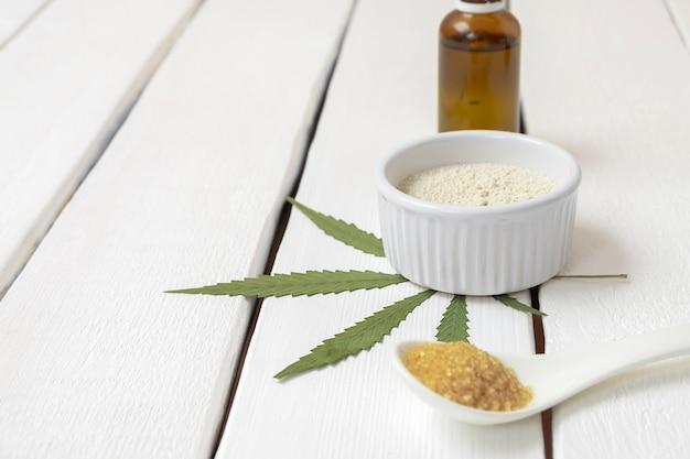 Prodotti infusi di cannabis farina di canapa zucchero di cannabis olio di cbd su fondo di legno bianco