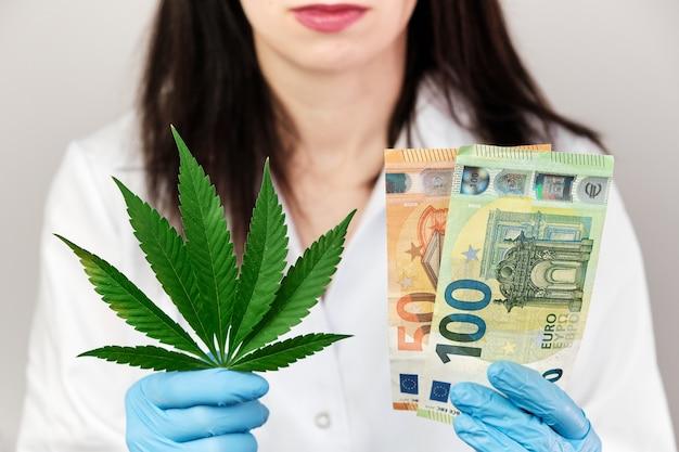Foglia di cannabis e banconota in euro nelle mani di donna in guanti di gomma e camice da laboratorio medico. entrate da prodotti realizzati con il concetto di cannabis. legalizzazione della marijuana.