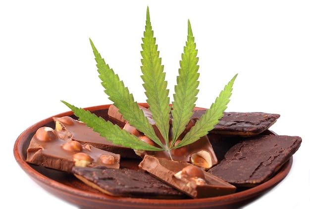 Foglia di cannabis con pezzi di cioccolato con noci su un piattino, cioccolato con cannabis cbd