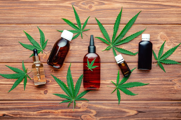 Liquidi medicinali e prodotti cosmetici alla cannabis. bottiglie di olio di canapa cbd e medicinali con piante di marijuana e foglie di erbaccia su fondo di legno marrone. pianta di marijuana medica cannabis sativa. vista dall'alto.