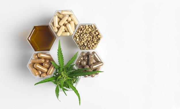 Capsule di medicina di cannabis, olio di canapa e semi e pianta verde in barattoli a nido d'ape su sfondo bianco