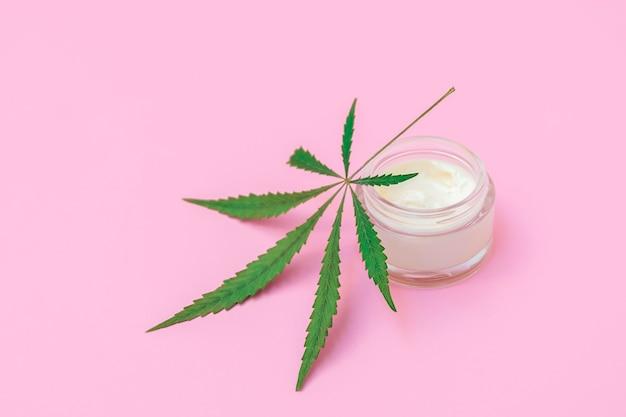 Concetto di cosmetici alla cannabis bottiglia di crema con foglia di canapa su sfondo rosa tenue con copia s...